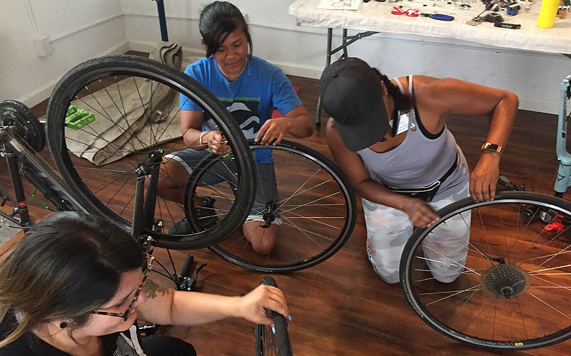 A group of ladies working together to repair bicycles
