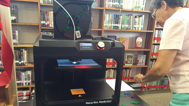 A volunteer assists with new 3D printing program at the Clairemont Library