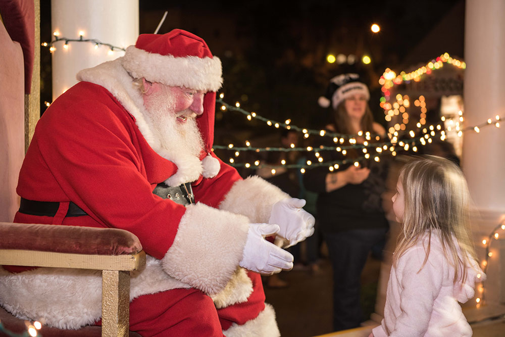 Santa Claus welcoming a child at December Nights 2017