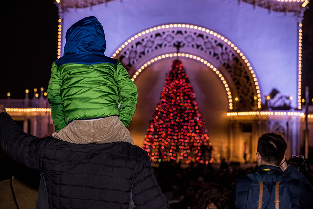 A child sitting on a man's shoulders while watching a performance at the Organ Pavilion during December Nights 2017