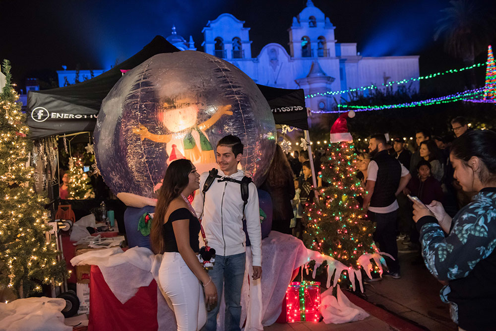 A couple taking a photo in front of a snow globe fixture at December Nights 2017
