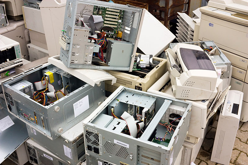 Computers and printer stacked for disposal