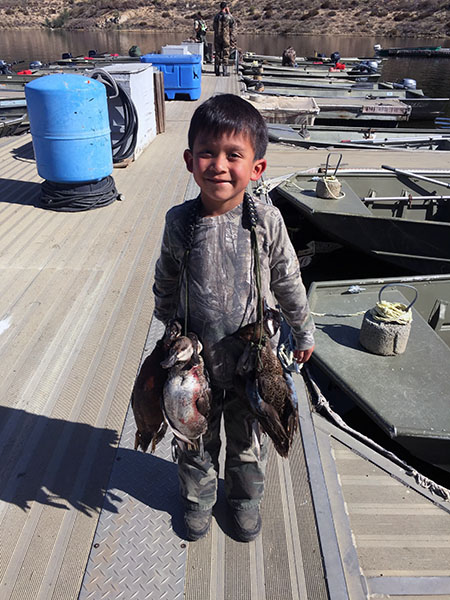 Young hunter displaying waterfowl caught at reservoir lake