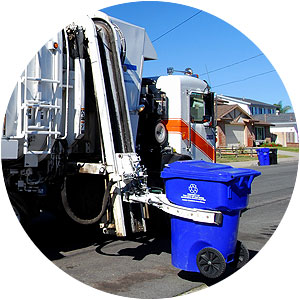 Garbage truck picking up recycling bin