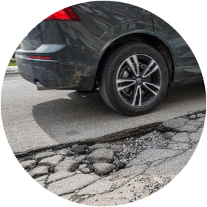 Car driving by a pothole on the street