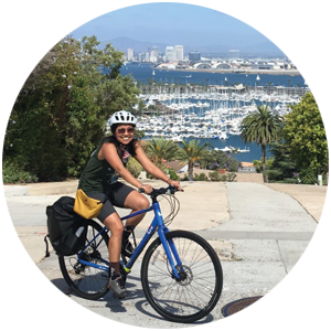 Jacq Le riding a bike with a view of downtown San Diego behind her