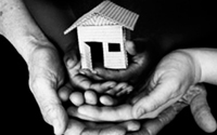 Photo of hands cradling a house