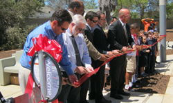 Photo of 	  Pictured left to right: 	  Serra Mesa Recreation Council Chair Jon Cima, 	  former Serra Mesa Recreation Council Chair George DeLaBarre, 	  Park and Recreation Director Herman Parker, 	  Transportation & Storm Water Deputy Director Drew Kleis, 	  Public Works ? Architectural Engineering and Parks Division Deputy Director Mark Nassar, 	  Councilmember Scott Sherman, 	  and children joining in the ribbon-cutting ceremony.