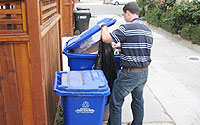Photo of Man Scavenging Through Trash Bin