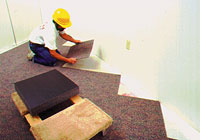 Photo of workman laying carpet