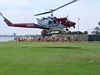 Picture of a helicopter landing on the field with kids in the background