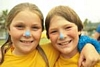 A picture of two girls with blue sunscreen on their nose