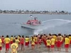 A lifeguard on a motor boat spraying water towards children on the beach