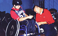 Photo of Volunteer Assisting Boy in Wheelchair