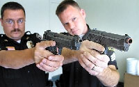 Photo of Police Officers Holding Real and Replicant Guns