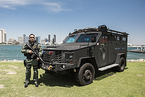 Photo of SWAT Officer next to a SWAT Truck