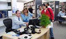 Photo of Branch Manager assisting library patrons at Mission Valley Branch Library in locating library materials