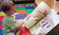 Photo of little boy fascinated with a big book at Central Library