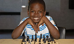 Photo of young chess club player ready for an opponent at Valencia Park/Malcolm X Library