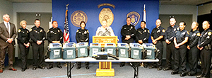 Photo of Councilmember Marti Emerald presenting the Police Department with 17 donated AEDs