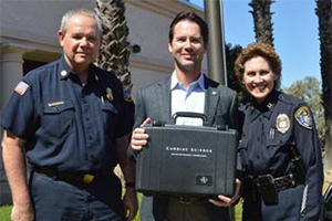 Photo of Councilmember Kersey presenting the Police Department with 32 donated AEDs