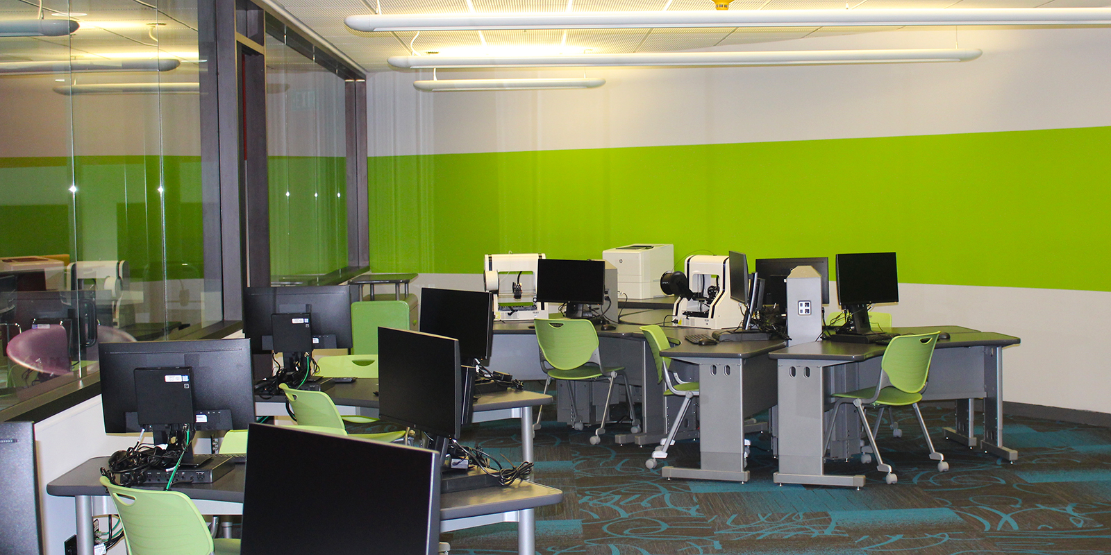 Photo of computers and 3D printer inside the Legler Benbough Teen IDEA Lab at the Valencia Park/Malcolm X Library.