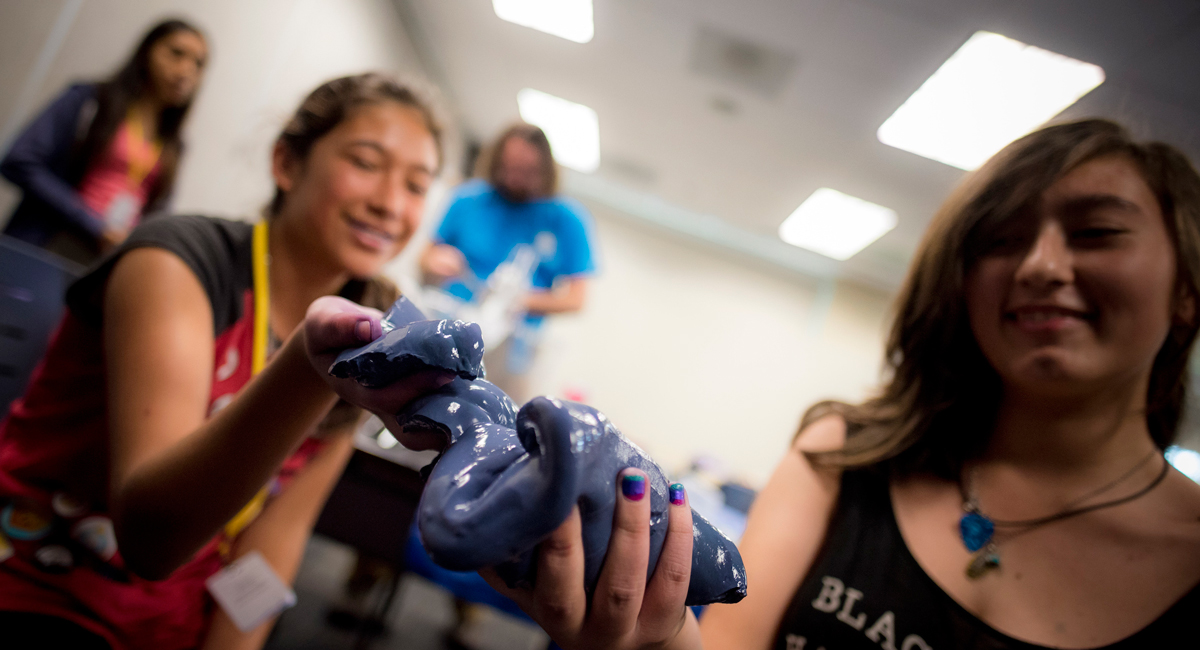 Photo of two students handling purple slime.