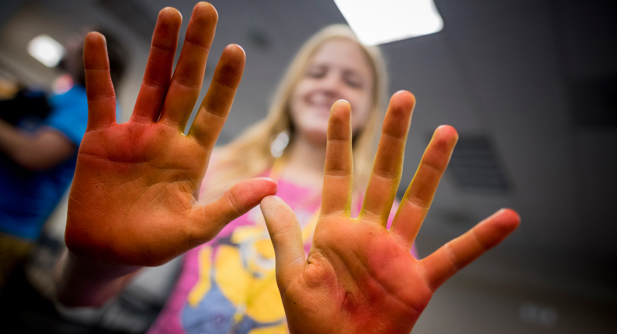 Photo of student's hand covered in red and orange pigments.