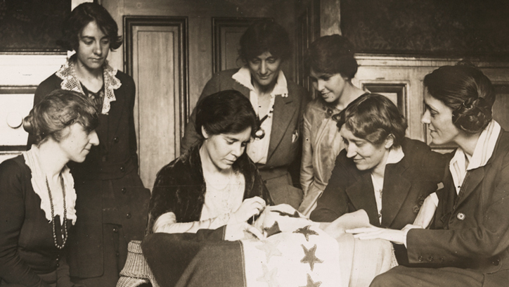 National Woman's Party activists watch Alice Paul sew a star onto the NWP Ratification Flag, representing another state's ratification of the 19th Amendment.