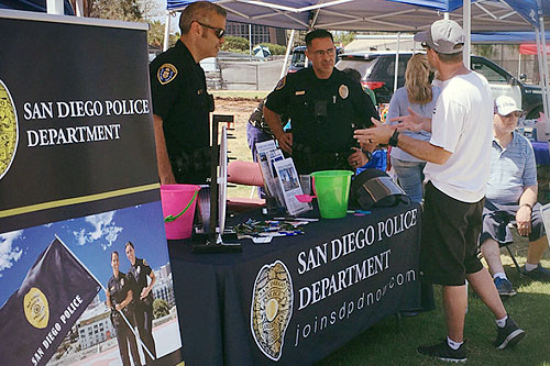 Two police officers speaking to a candidate at a recruiting event