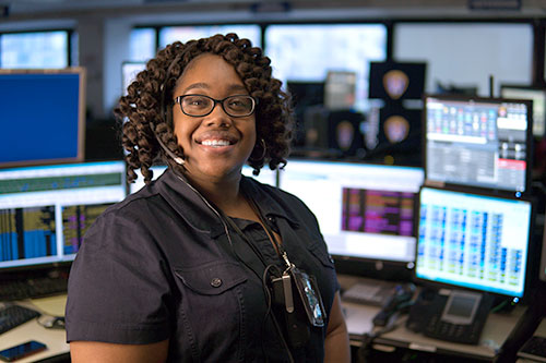 San Diego Police dispatcher smiling in front of her workstation