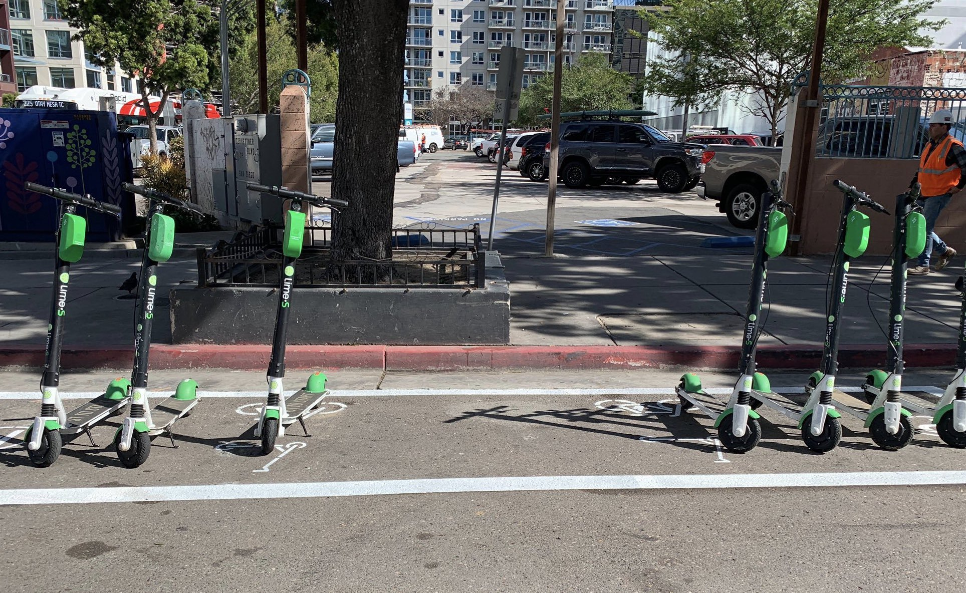 Dockless bikes parked in a dedicated scooter corral on a street.