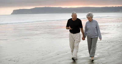 A senior couple walking on the beach at sunset