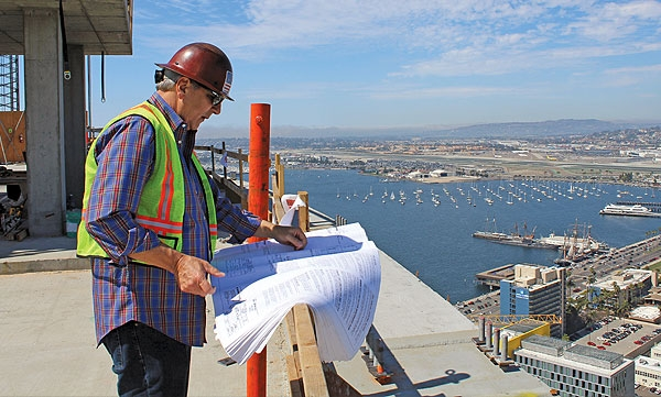 Construction worker reviewing plans in a building being constructed in downtown San Diego