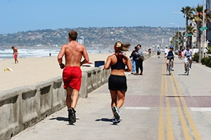 Photo of Couple Running on Boardwalk