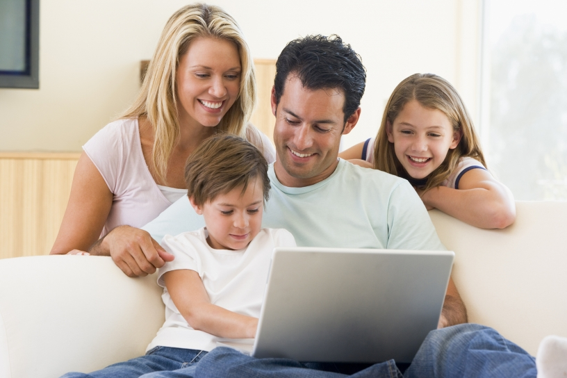Family looking at a laptop monitor