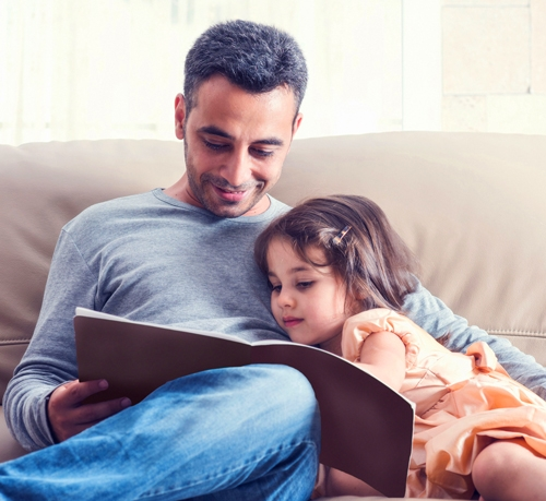 Father reading book to young daughter.