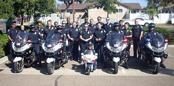 Group photo of police officers behind police motorcycles