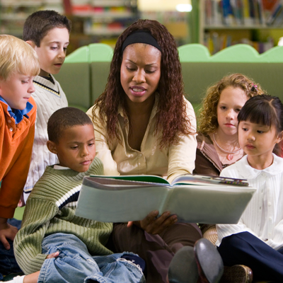 Image of person reading books to children
