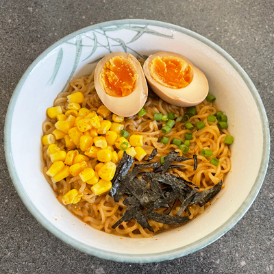Image of a bowl of ramen with egg and corn