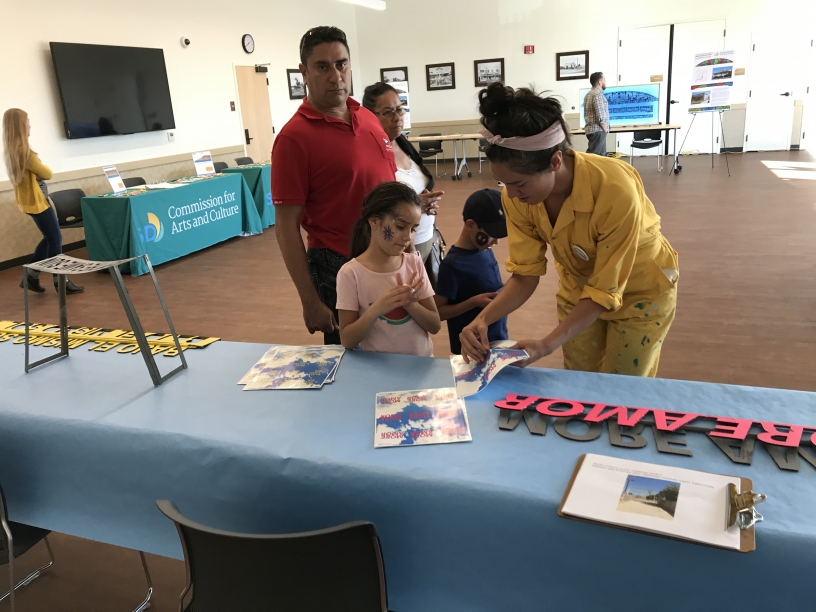 Artist Janelle Iglesias gives a little girl a sticker that has text from her proposed artwork. on the table in front of them are cardboard text mock-ups of phrases the artist is considering for the art project such as more amore.