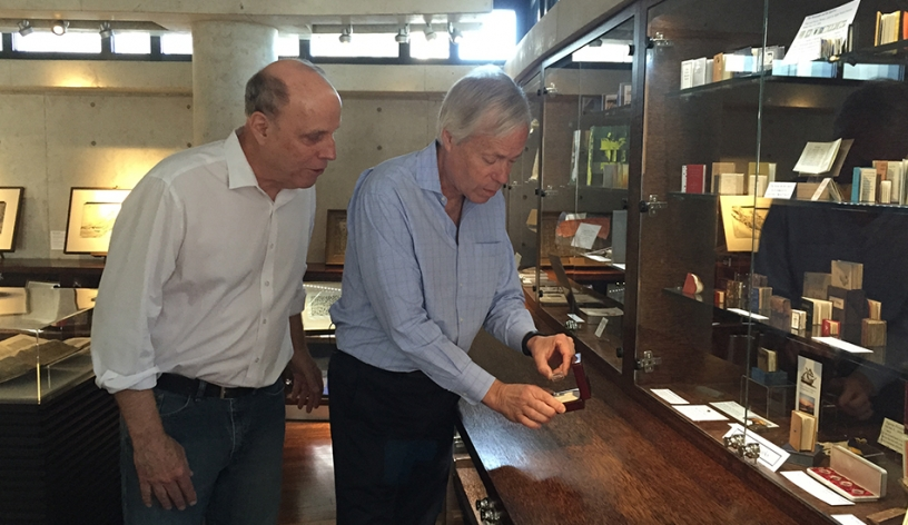 Photo of reporter Ken Kramer and Special Collections librarian Rick Crawford examining one of the world's smallest book.