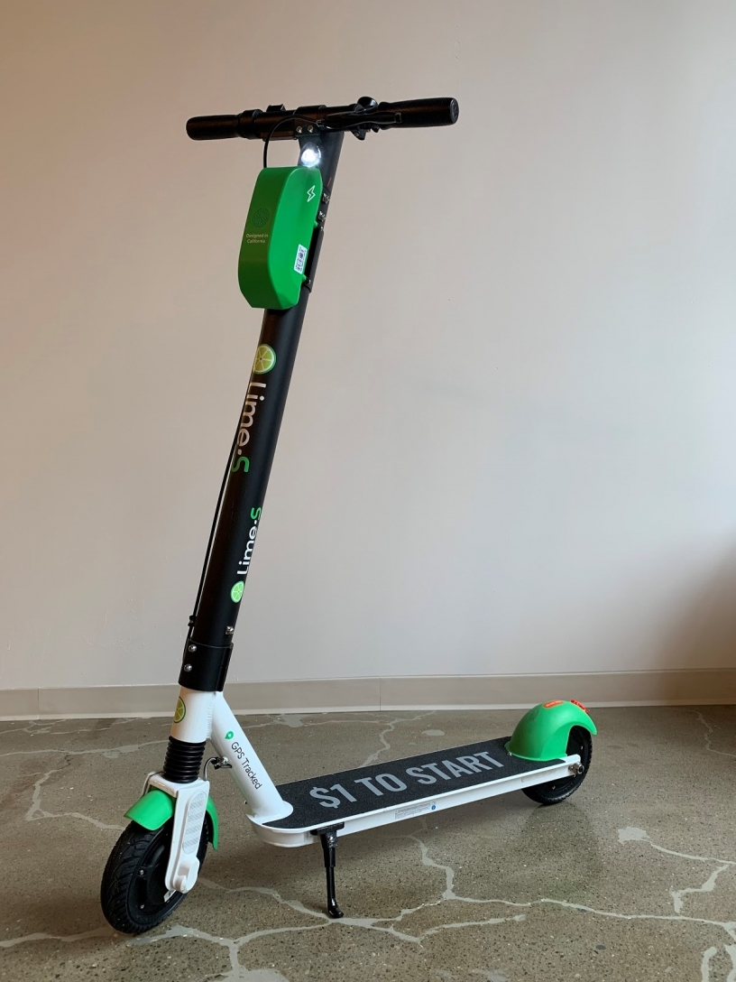 A picture of a black Lime scooter with white and green trim.