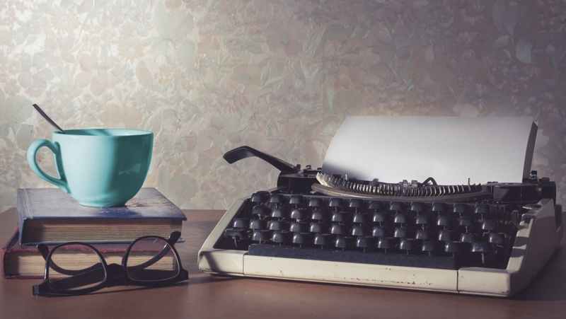 Photo of typewriter with book and cup.