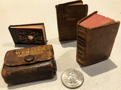Image of four miniature books next to a quarter for size comparison