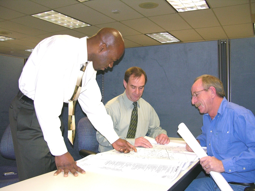 three men reviewing permit application