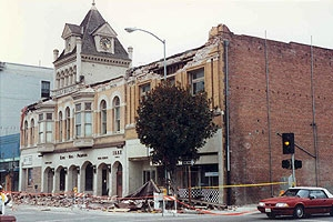 An earthquake-damaged unreinforced masonry building with its parapets collapsed onto the sidewalk.