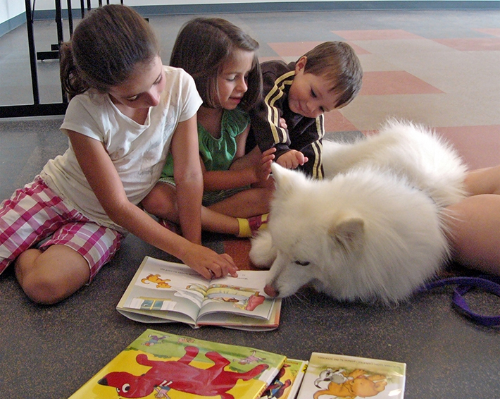 Erin Gillum reads to dog Bitsy with sister Sidney and brother Garrett