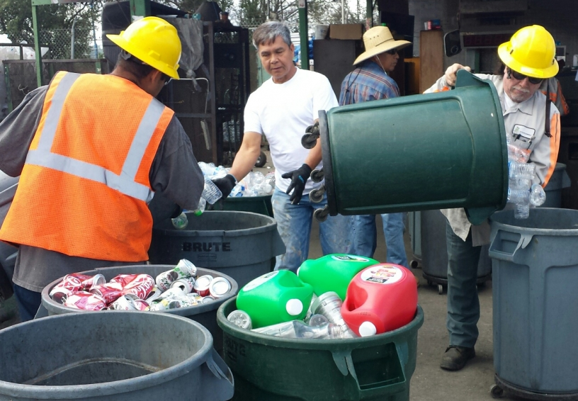 Several men sorting items into bins for recycling