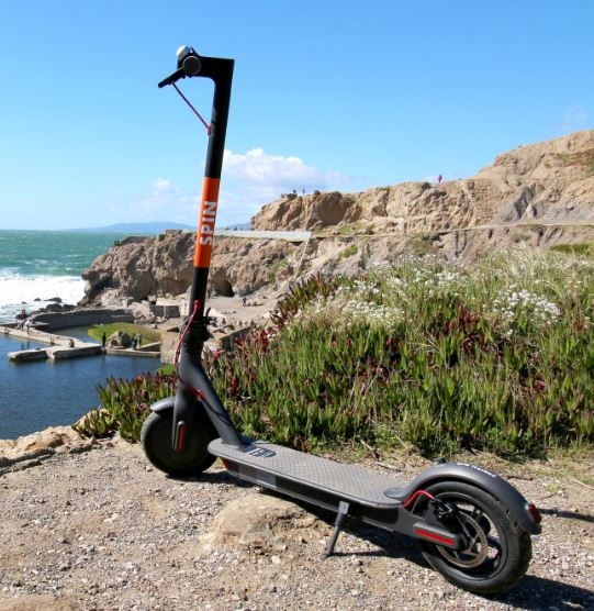 A shared mobility device from Spin parked on a mountain overlooking the ocean.
